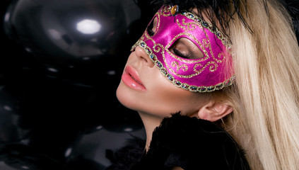 Beautiful sensual blonde woman with carnival mask on her face stands on a background of black balloons and sexy looks into the lens