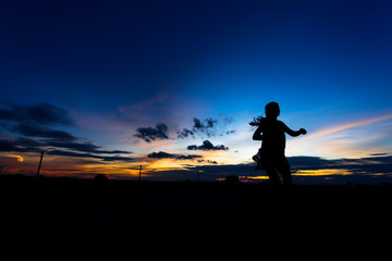 Silhouette of woman posing at sunset or sunrise