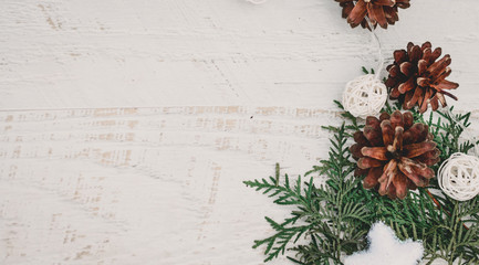 Christmas background with pine cones, sprigs of arborvitae and shiny  Christmas toy star on a white wooden background