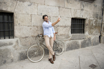young happy man taking selfie with mobile phone on retro cool vintage bike