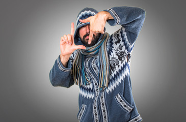 Man with winter clothes focusing with his fingers on grey background