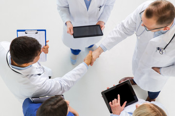 doctors with tablet pc doing handshake at hospital