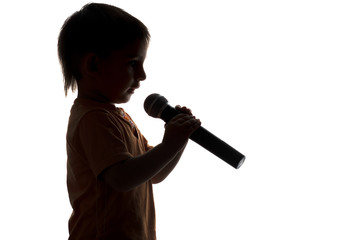 silhouette of little boy singing karaoke into microphone