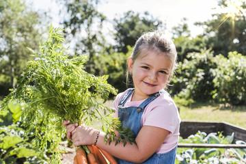 Portrait of smiling girl in garden holding bunch of carrots