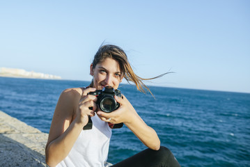 Portrait of smiling young woman with camera at the sea