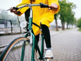 Close up of woman wearing raincoat while riding bicycle