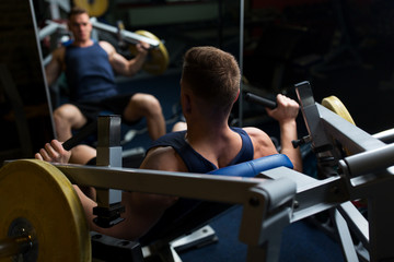 man doing chest press on exercise machine in gym