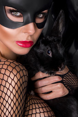 beautiful young sexy model in a black carnival mask, rabbit ears, holding the hands of a living rabbit witht the black balloons and sensually looks at the camera, wearing a bodystocking with mesh