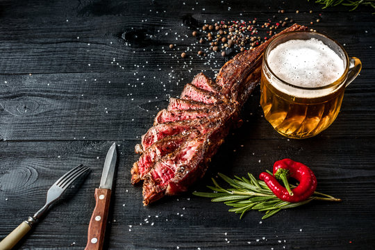 Barbecue dry aged rib of beef with spice, vegetables and a glass of light beer close-up on black wooden background