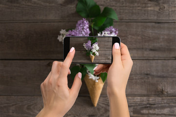 Photographer blogging workshop concept. Hand holding phone and taking photo of flowers.