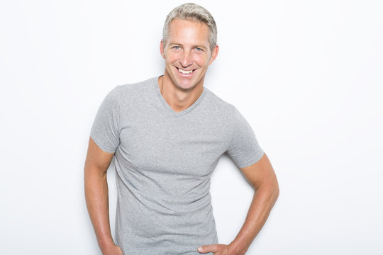 Portrait of confident mature man standing on white background