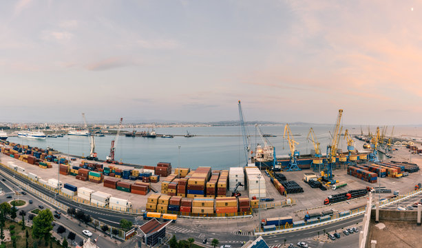 Panorama of the cargo terminal of the international port of Durres at sunset. Unloading of the tanker by cargo cranes. A platform for storing sea freight containers.