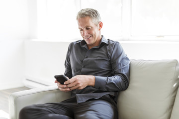 Portrait of mature man relaxing at home in sofa and cellphone
