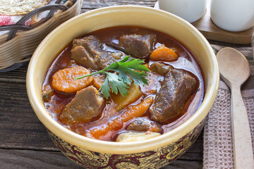 Stew with meat and vegetable in ceramic bowl on table