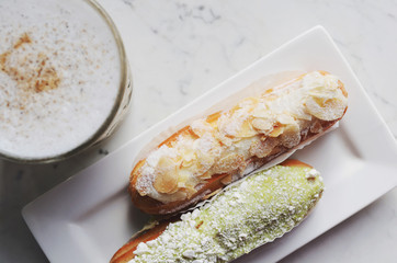 Almond and pistachio eclairs and latte, top view