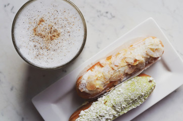 Latte topped with cinnamon and cardamom and two eclairs on marble table