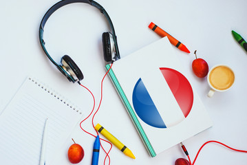 the book with french flag and headphones. concept of french learning through audio courses