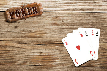 poker sign and four aces on wooden background