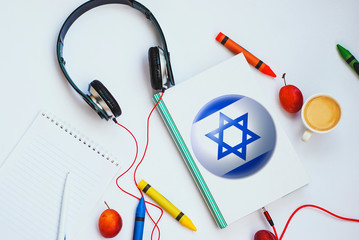 the book with israel flag and headphones. concept of Hebrew learning through audio courses