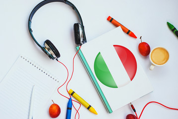 the book with italian flag and headphones. concept of italian learning through audio courses