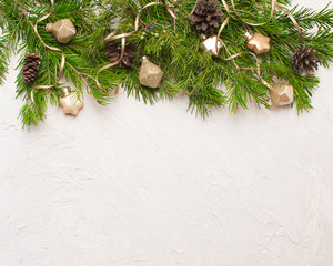 Christmas or New Year background: fur-tree branches, gold glass balls and toy, decoration and cones on a white background