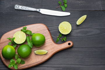 Fresh limes on cutting board on wooden table. Top view, background.