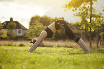 Young brunette doing yoga and stretching back park during sunset