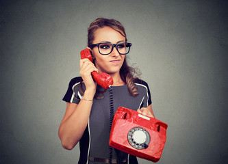 Grumpy displeased young woman having unpleasant phone conversation