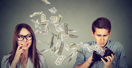Sad man looking at his wallet with money dollar banknotes flying away towards flirting cute young woman