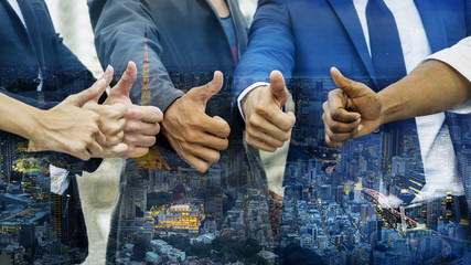 thump up hand from the group of business people with the overlay top view of nighttime modern city background.