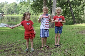 Three happy children waving American flag in patriotic clothes whilst celebrating the Fourth of July