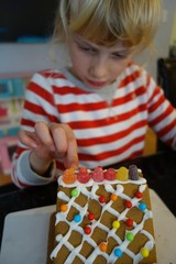 Little girl decorating a gingerbread house for Christmas
