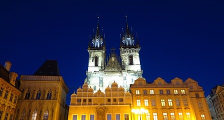 Prague Tyn Church towers over Baroque buildings in Old Town Square at night