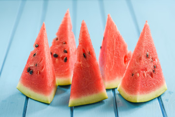 Fresh juicy watermelon with seeds cut into triangles on bright blue background