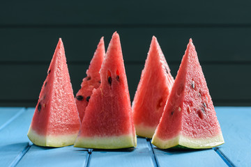 Bright red juicy watermelon cut into high triangles standing on blue table