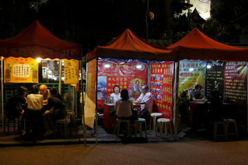 Fortunetellers talk with their customers at Temple Street in Hong Kong
