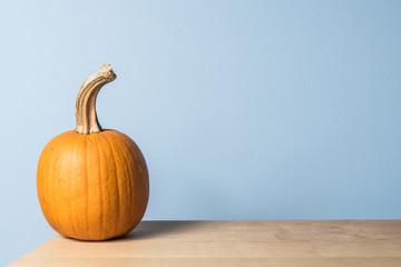 A homegrown fresh orange sugar pumpkin sits on a handmade maple wood table, against a blue wall.
