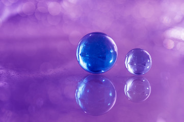 Two blue glass balls on a glass table. Glass balls on a purple background with reflection.