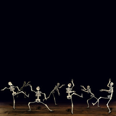 Halloween skeleton monsters dancing. Black background.