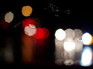 blurry traffic jam bokeh light view outside road from inside a car while raining , night cityscape of abstract background