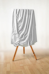 covered painting on an easel, white cloth over the picture, wooden floor and light background, art concept for an exhibition opening day or a presentation ceremony, copy space