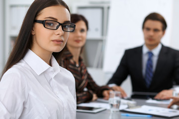 Group of business people at meeting on the background of office. Focus on a beautiful brunette