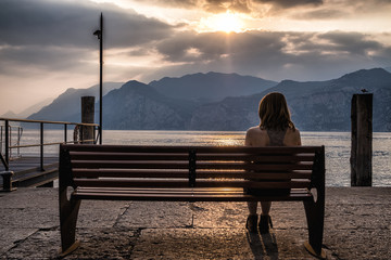 Girl on bench at sunset at an Italien lake