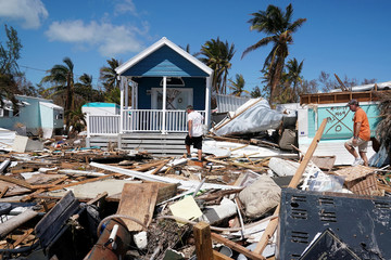 Residents walk though a debris field of former houses following Hurricane Irma in Islamorada