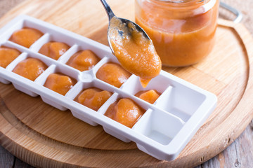 Baby food homemade in ice cubes tray ready to be frozen