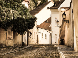 Old medieval narrow cobbled street and small ancient houses of Novy Svet, Hradcany district, Prague, Czech Republic. Vintage sepia style image