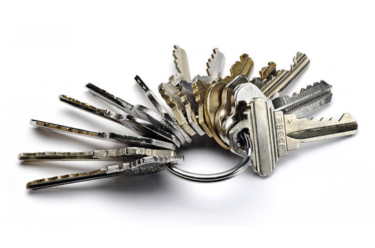 Close up of metal key ring with many worn keys isolated on white