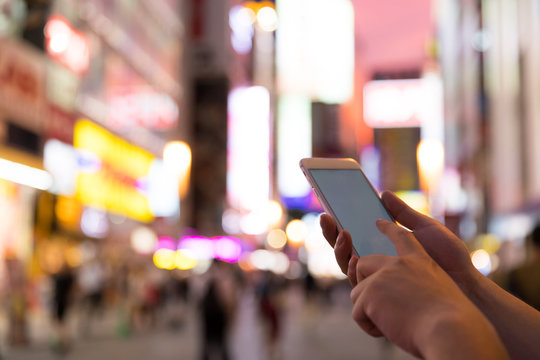 a man using smart phone in akihabara