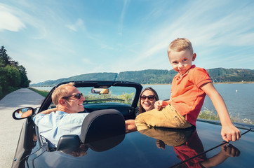 Family traveling by cabriolet car