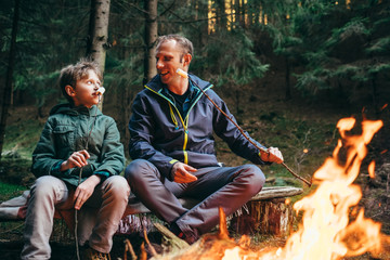 Father and son roast marshmallow candies on the campfire in forest